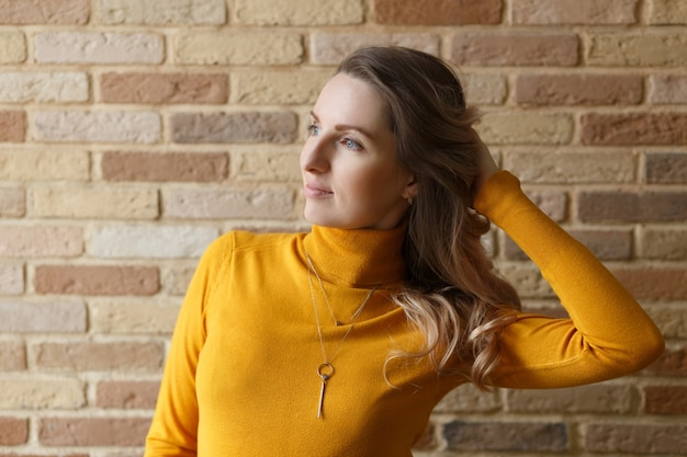 Thoughtful pregnant woman in yellow cardigan caressing her belly and posing near by brick wall