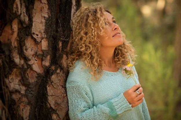 사려깊은 예쁜 성인 백인 여성이 꽃을 손에 들고 숲속의 휴식 여가 활동에서 공중을 바라보며 환경 개념과 행성 사람들을 구합니다.