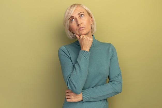 思いやりのあるかなり金髪のスラブ女性はあごを保持し、孤立して見上げる