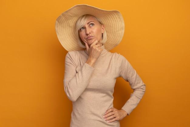 ビーチ帽子をかぶった思いやりのあるきれいな金髪のスラブ女性は、オレンジ色の側を見ているあごを保持します