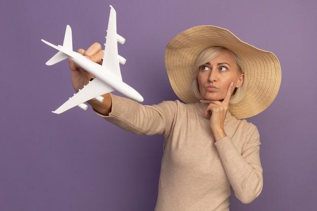 ビーチ帽子をかぶった思いやりのあるきれいな金髪のスラブ女性は、あごに手を置き、紫色の側面を見て模型飛行機を保持します