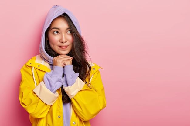 思いやりのあるかわいいブルネットの韓国の女の子は、あごの下で手を一緒に保ち、脇を見て、頭に紫色のフードをかぶっています