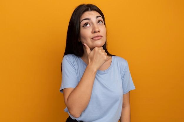 Premurosa bella donna castana mette la mano sul mento e guarda in alto isolato sulla parete arancione
