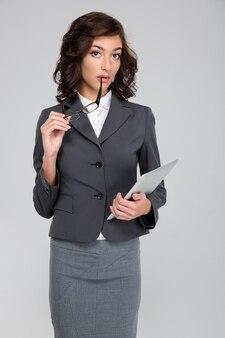 안경 및 태블릿을 들고 회색 의상 사려 깊은 꽤 곱슬 집중된 비즈니스 우먼
