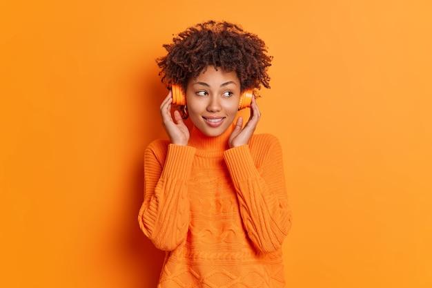 아프로 머리카락을 가진 사려 깊은 예쁜 밀레 니얼 여성은 옆으로 집중된 음악을 듣는다.