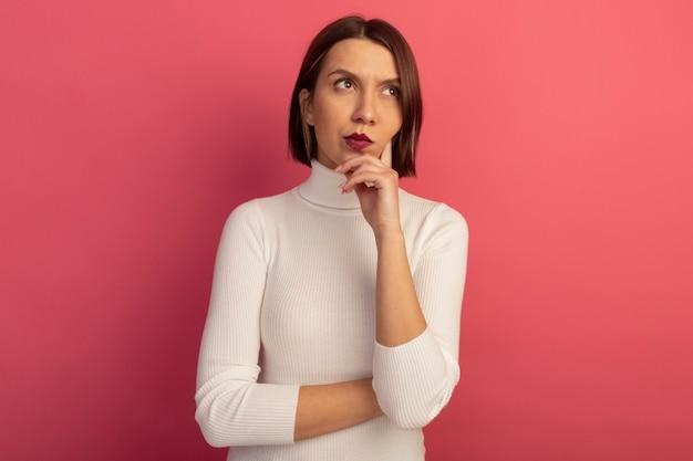 思いやりのあるきれいな女性はあごに手を置き、ピンクの壁に隔離された側を見て
