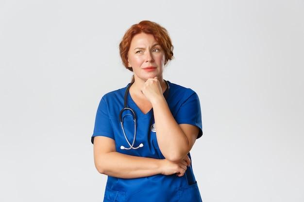 スクラブで思いやりのあるプロの中年女性医師、外科医が仮定または選択を行う