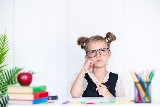 Заботливый ученик за партой. девушка в классе с карандашами, книгами. малыш девочка из начальной школы.