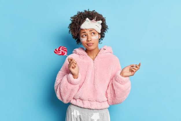 Thoughtful puzzled curly haired woman raises palm concentrated somewhere pensively wears sleepmask and pajama holds sweet candy on stick applies skin care night products on face