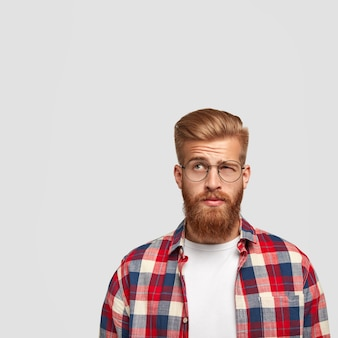 Thoughtful puzzled man has thick ginger beard looks with hesitation upwards, doesn`t know what to do after graduation
