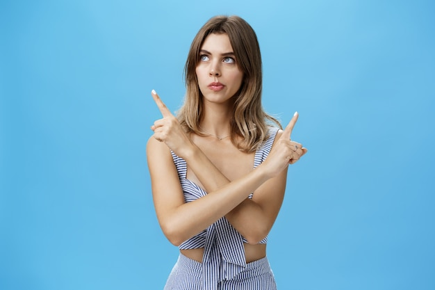 Thoughtful questioned attractive female coworker trying make choice facing hard decision crossing hands against chest pointing left and right looking focused while thinking over blue wall.