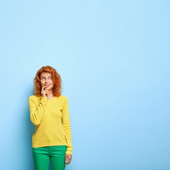 思いやりのある赤い髪の女性は唇に指を置き、何かについて考えます