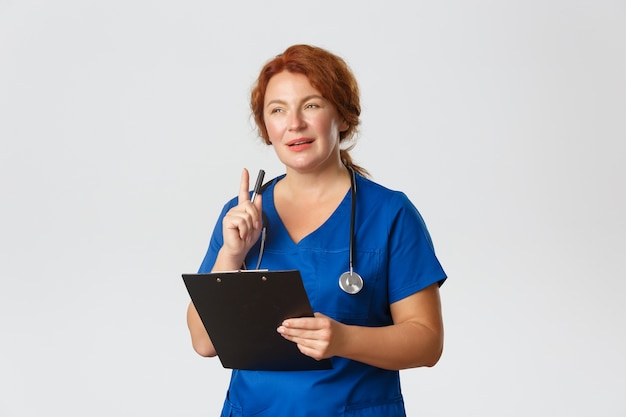 Thoughtful redhead female doctor, redhead physician in blue scrubs looking intrigued with patient case, shaking pen and holding clipboard