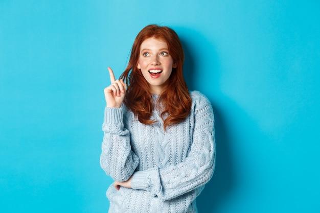 考えを持って、指を上げて、青い背景の上に立って、良い計画に満足して笑っている思いやりのある赤毛の女の子。