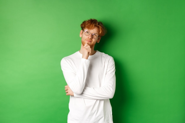 Thoughtful redhead man in glasses making choice, looking up and thinking, standing over green background.