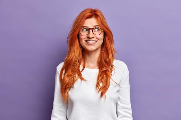 思いやりのある赤毛のきれいな女性が目をそらし、笑顔でカジュアルな服を着ているものを優しく考えます。