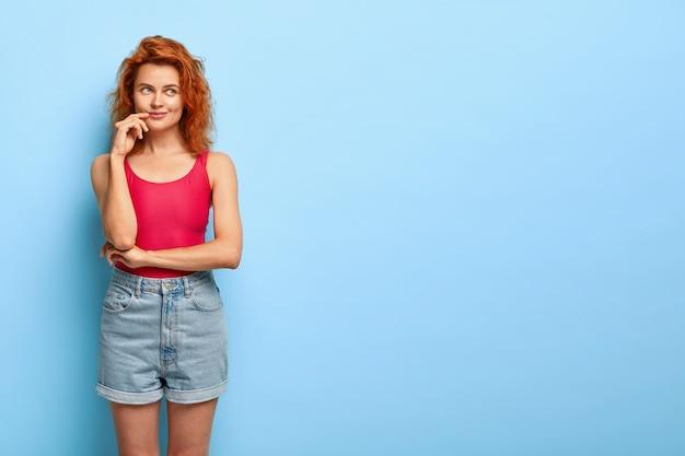 思いやりのある赤毛の女性は満足して夢のように感じ、何かを考えます
