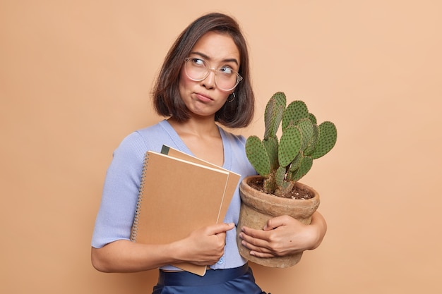Thoughtful sad asian female student tired of distance studying holds notepads and potted cactus wears big transparent glasses looks away thinks deeply about something isolated over beige wall