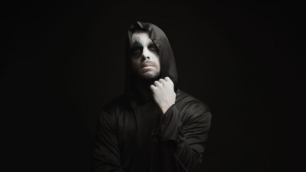 黒の背景に思いやりのある恐ろしい死神。ハロウィーンの悪魔。