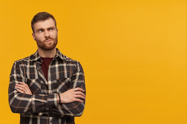 Thoughtful sceptical young man in checkered shirt with beard keeps arms crossed and thinking over yellow wall looking away to the side