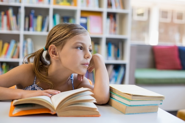 Thoughtful school girl reading book in library