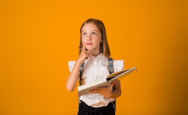 교복을 입고 배낭을 메고 있는 사려깊은 여학생은 텍스트를 넣을 수 있는 노란색 배경에 펜이 달린 공책을 들고 있습니다