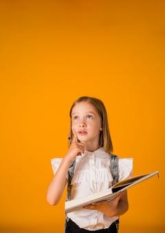 교복을 입은 사려깊은 여학생은 노란색 배경에 펜이 달린 파란색 공책을 들고 공간 사본을 가지고 있습니다
