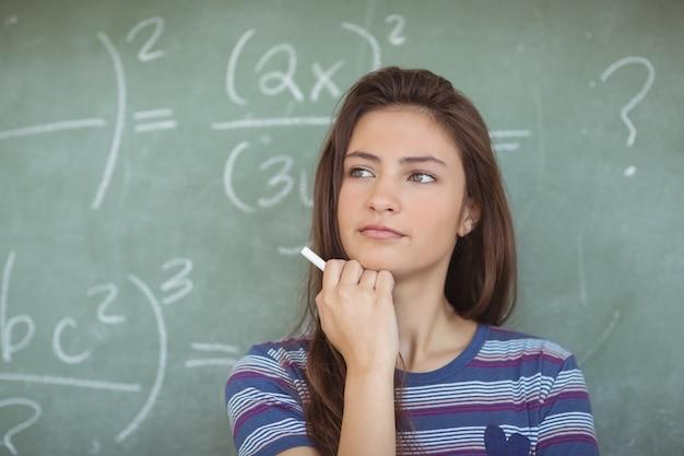 Thoughtful schoolgirl pretending to be a teacher in classroom