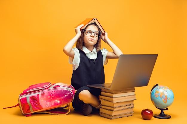 사려깊은 여학생은 책 더미 뒤에 앉아 있고 노트북은 머리 어린이 교육에 관한 책을 가지고 있습니다