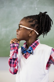 Thoughtful schoolgirl standing with hand on chin in classroom