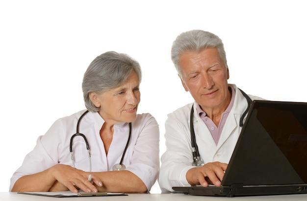 ノートパソコンでテーブルに座っている思いやりのある先輩医師