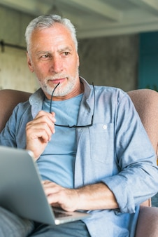 Thoughtful senior man holding eyeglasses sitting in armchair with laptop