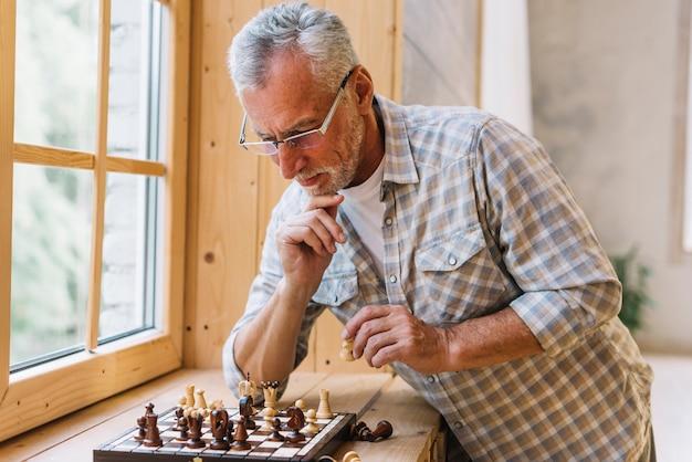 Задумчивый старший мужчина играет в шахматы возле окна