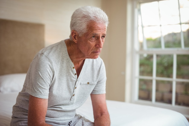 Thoughtful senior man sitting on bed