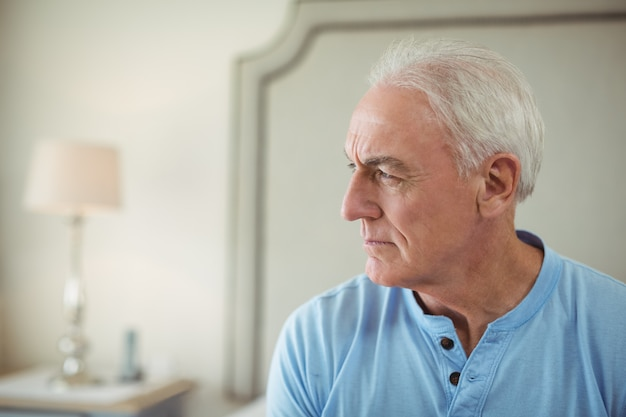 Вдумчивый старший мужчина, сидя в спальне