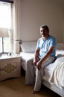 Вдумчивый старший мужчина, сидя на кровати