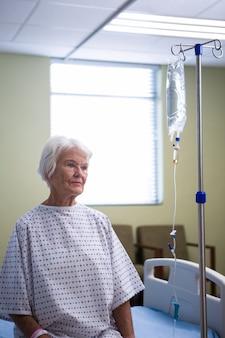 病院で立っている思いやりのある上級の患者