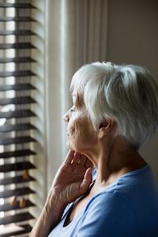 집에서 창에서 바라 보는 사려 깊은 고위 여자