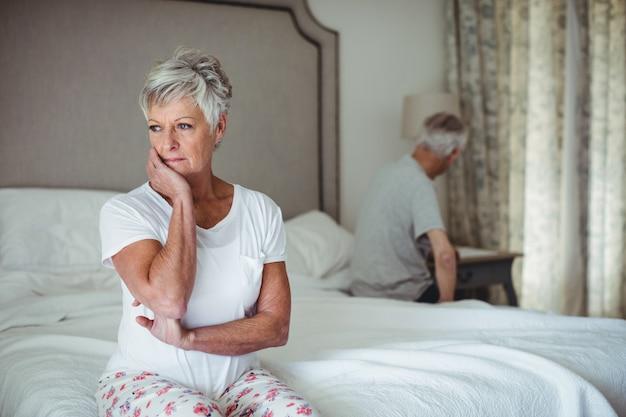 ベッドルームに座っている思いやりのある年配の女性