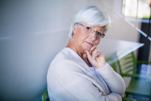Заботливая старшая женщина сидя на стуле
