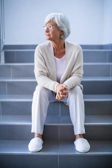 Вдумчивый старший женщина сидит на лестнице