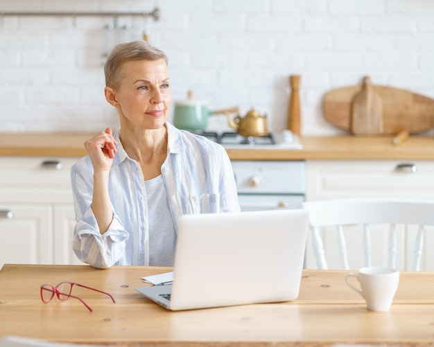 Thoughtful senior woman with laptop looking away