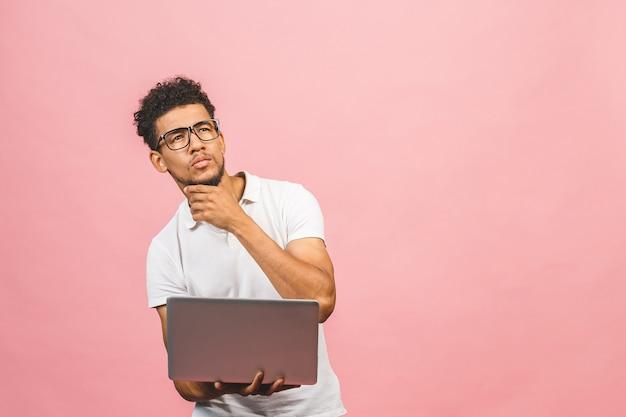 분홍색 배경에 고립 된 노트북과 사려 깊은 심각한 아프리카 계 미국인 남자