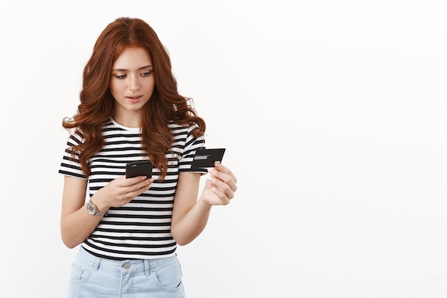 Thoughtful serious-looking cute redhead female in striped t-shirt input credit card number in smartphone, open online bank account, paying for internet purchase, shopping