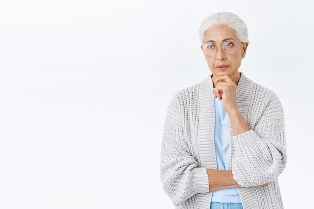Thoughtful, serious-looking focused senior lady in glasses with grey hair combed, wear winter cardigan, touch chin pensive, look sideways as trying understand something, thinking what do
