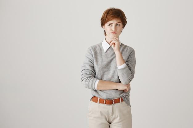짧은 머리는 흰 벽에 포즈와 사려 깊은 심각한 빨간 머리 소녀