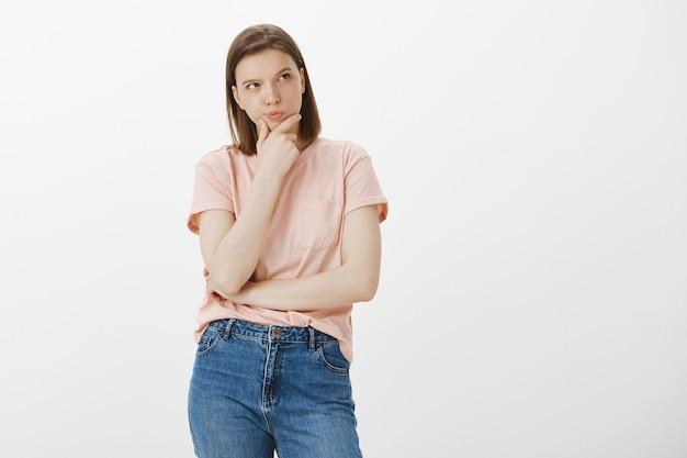 Задумчивая серьезная женщина ищет решение, думает, обдумывает выбор и смотрит в правый верхний угол