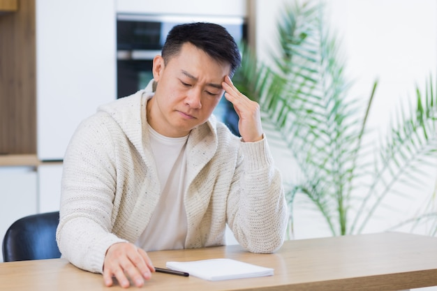 Thoughtful serious young asian man looking away student writer sit at home office desk with laptop