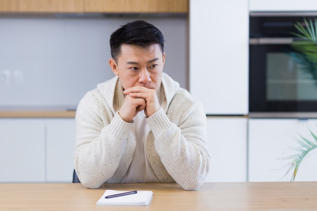 Thoughtful serious young asian man looking away student writer sit at home office desk