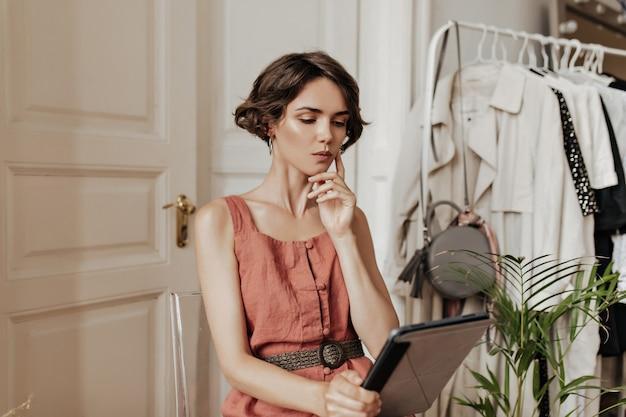 リネンの赤いドレスを着た思いやりのある短い髪の若い女性は、居心地の良い明るい部屋の椅子に座って、コンピューターのテーブルを保持します。